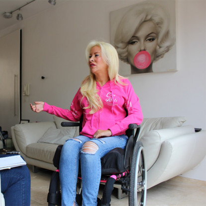 Blond haired woman in a pink top and jeans sitting in a wheelchair